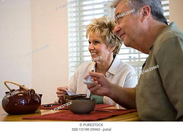 Mature couple having food at a dining table