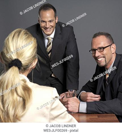 Business people having meeting at conference table, smiling