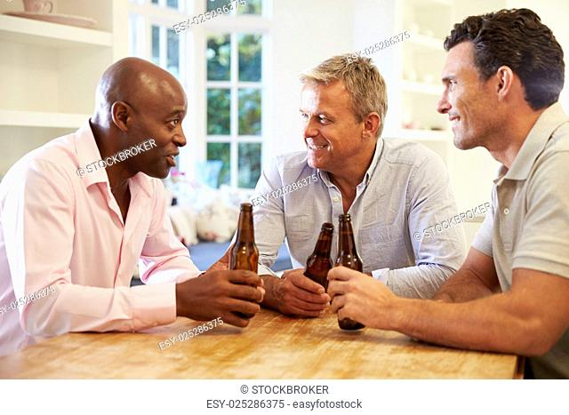 Mature Male Friends Sit At Table Drinking Beer And Talking