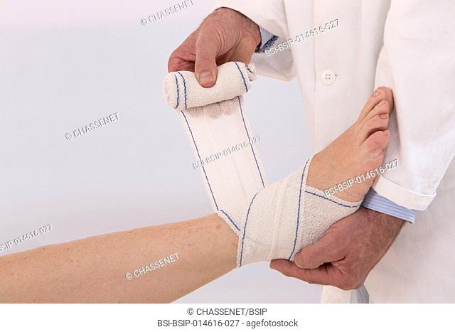 Doctor bandaging a patient's ankle