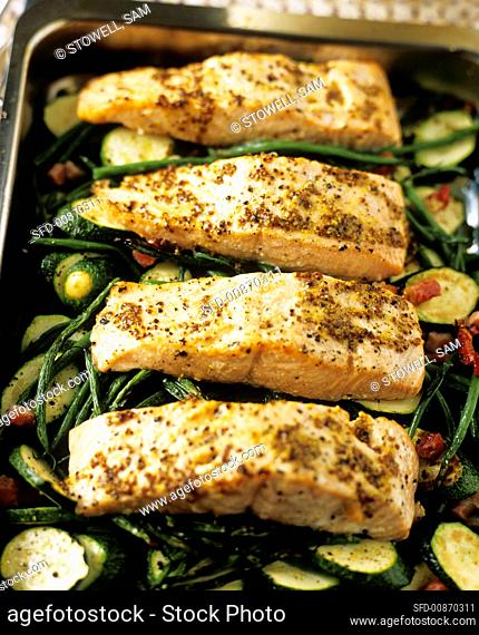 Salmon fillet with mustard seeds on courgettes and beans