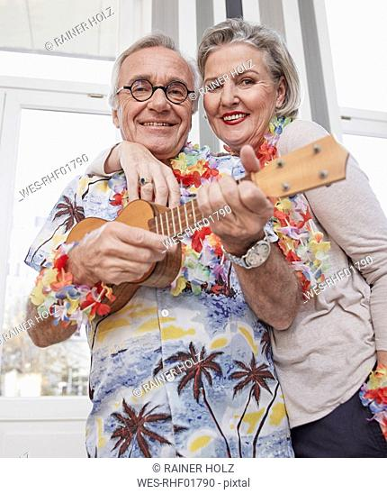 Happy senior couple with man in Hawaiian shirt playing ukulele