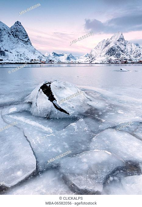 The frozen sea and the snowy peaks frame the fishing village at sunset Reine Nordland Lofoten Islands Norway Europe
