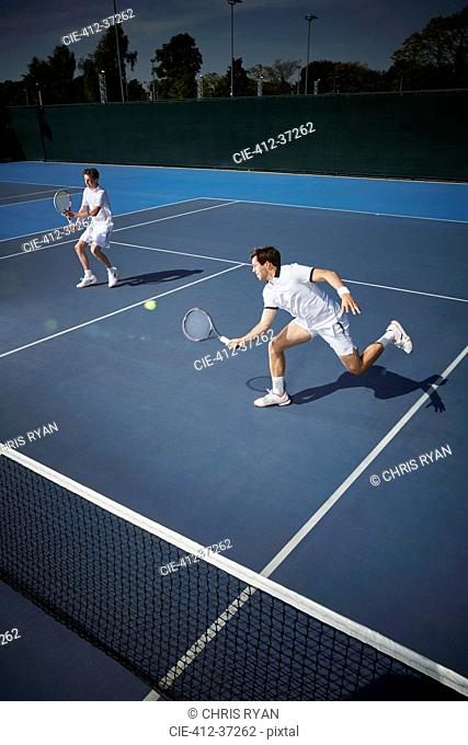 Young male tennis doubles players playing tennis, reaching for the ball on sunny blue tennis court