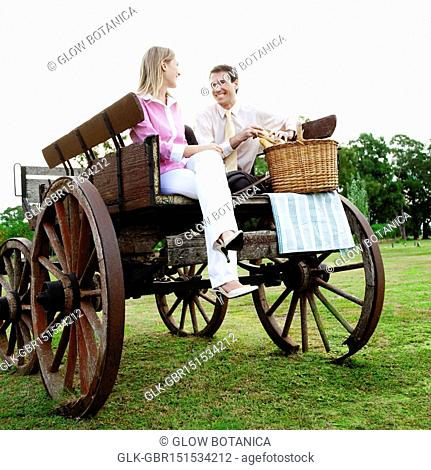 Couple sitting on a carriage with a picnic basket