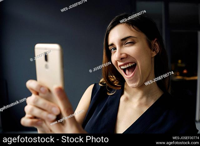 Portrait of young woman with smartphone pulling funny faces