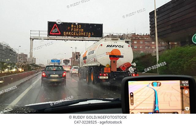 Cars and trucks traffic on a rainy day travelling towards Barcelona on the Highway. the GPS indicates the route. Barcelona. Cataluña. Spain