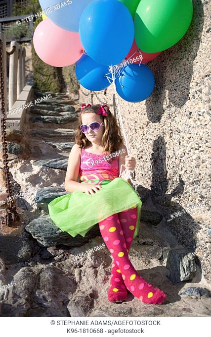 one little girl sitting on stone steps holding balloons