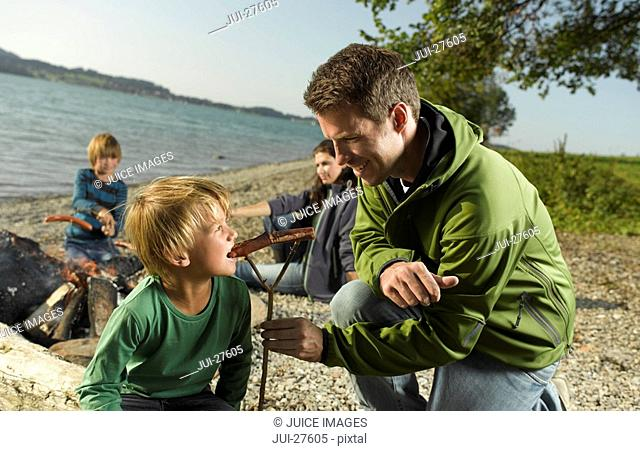 A family cooking sausages on a campfire beside a lake