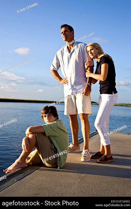 Father and teenage children on dock