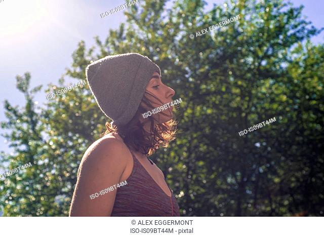 Young woman in knitted hat contemplating in front of tree foliage, backlit head and shoulder profile