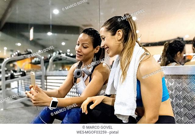 Two women having fun with their smartphone after work out in the gym