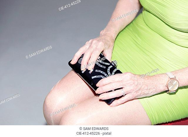 Senior woman in dress holding clutch purse