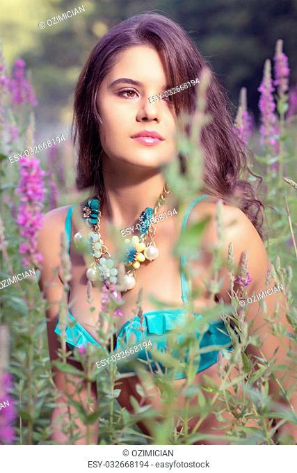 Beautiful young girl standing in high grass and flowers on river bank wearing bra and jeans shorts