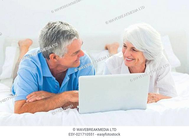 Couple lying and using a laptop pc in bed