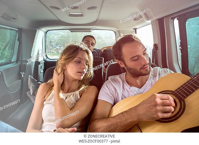Man with friends in a car playing guitar