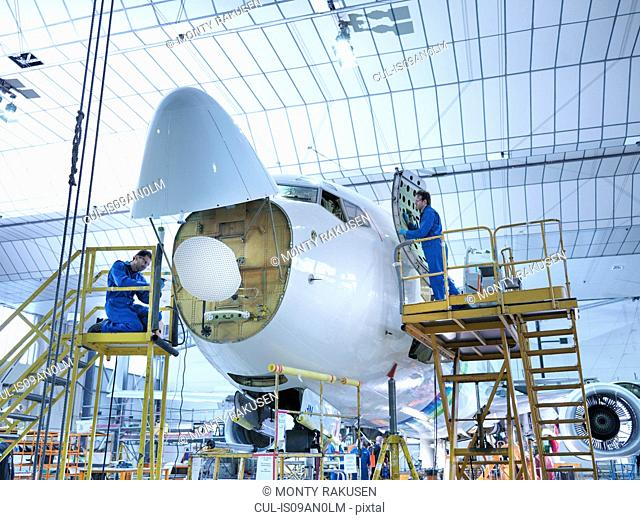 Engineers working on aircraft in aircraft maintenance factory