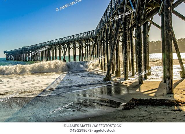 Waves crash beneath a wooden pier on the Pacific coast of California