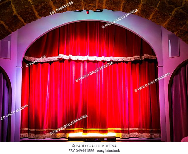 A red curtain in an old and very small Italian theatre