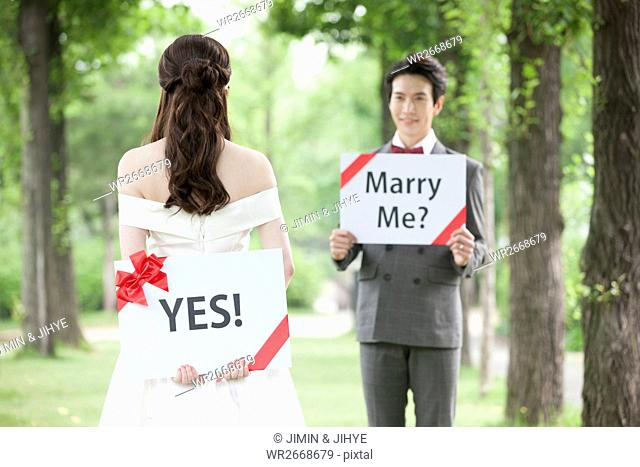 Young wedding couple with English messages posing face to face outdoors
