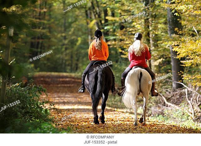 two girls riding on Noriker horse black and Arabian horse white