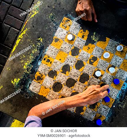 A hand of a Salvadoran man is seen moving a plastic bottle cap while playing checkers on an outdoor checkerboard table in the park in San Salvador, El Salvador