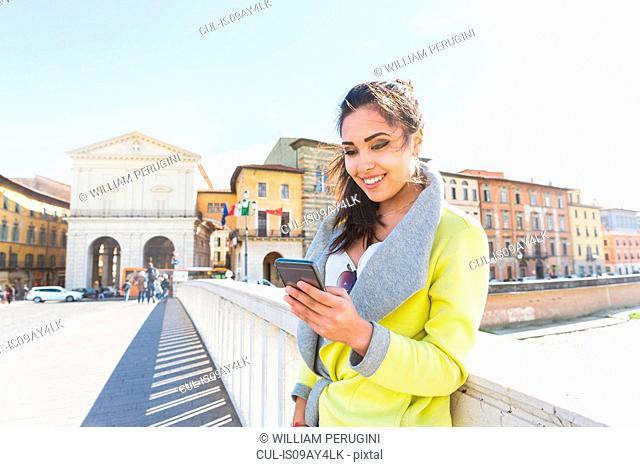 Woman on bridge looking at smartphone smiling