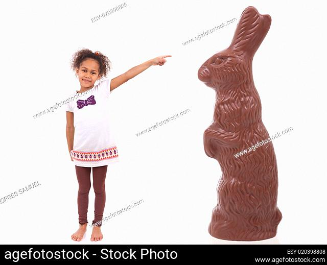 African Asian girl pointing a giant chocolate rabbit