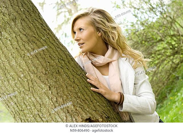 Beautiful young woman enjoying being outside in a green natural environment She is touching a tree in a contemporary twist on the idea of tree huggers