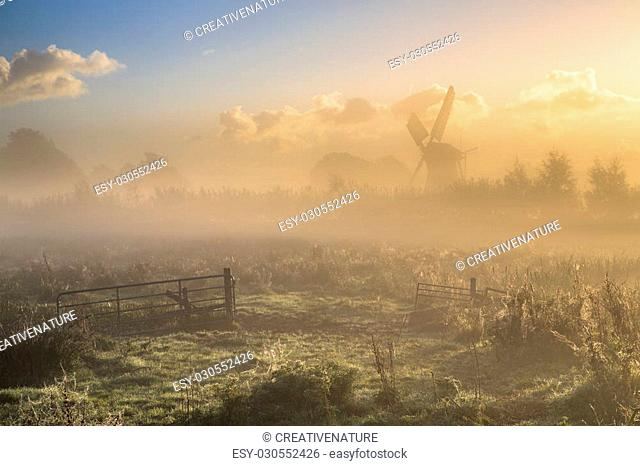 Morning fog over farmland with gate in foreground and wooden windmill in background