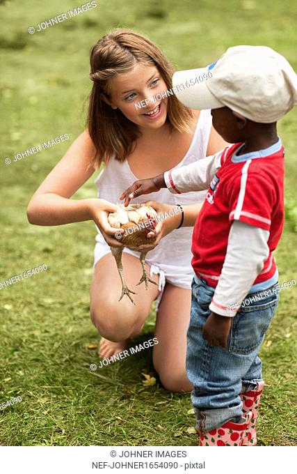 Girl and boy stroking hen