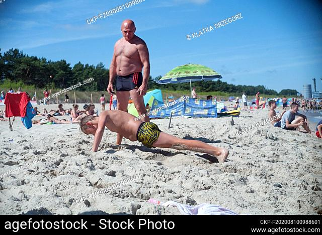 Poland, Wladyslawowo 10.08.2015. Summer camps in popular Polish seaside resort. Here: The boy does push-ups for punishment under the supervision of educator