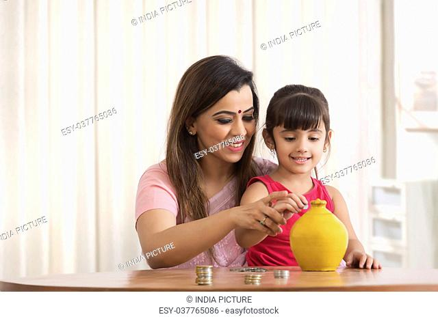 Mother and daughter putting coins in piggy bank