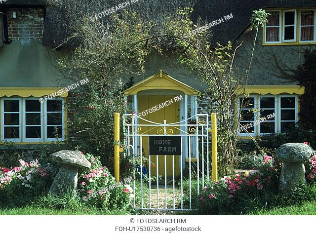 Staddlestones on either side of yellow and white metal gate in front of cottage with yellow gable above windows