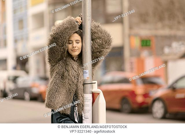 smiling sensitive woman with closed eyes leaning on lamppost at street in city, positive minded, happy, Munich, Germany