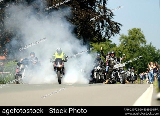 24 July 2021, Lower Saxony, Rhauderfehn: Motorcyclists ride past the house of Kilian, a cancer patient. Thousands of bikers have followed the calls to give the...