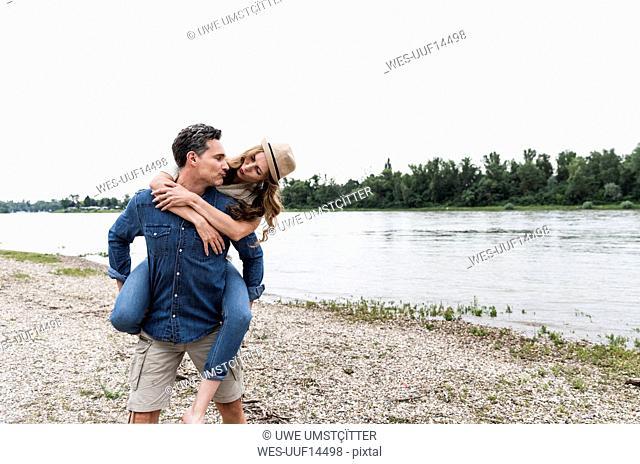 Man carrying girlfriend piggyback at the riverside