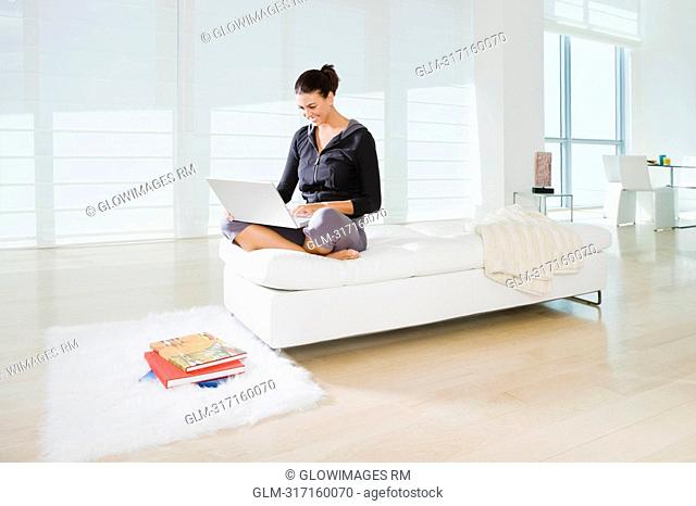 Young woman sitting on the bed and using a laptop