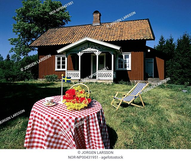A table with swedish flag and chair in front of red cottage