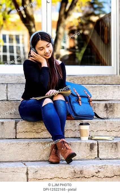 A young Chinese female university student sits on the steps listening to music using headphones with eyes closed; Edmonton, Alberta, Canada