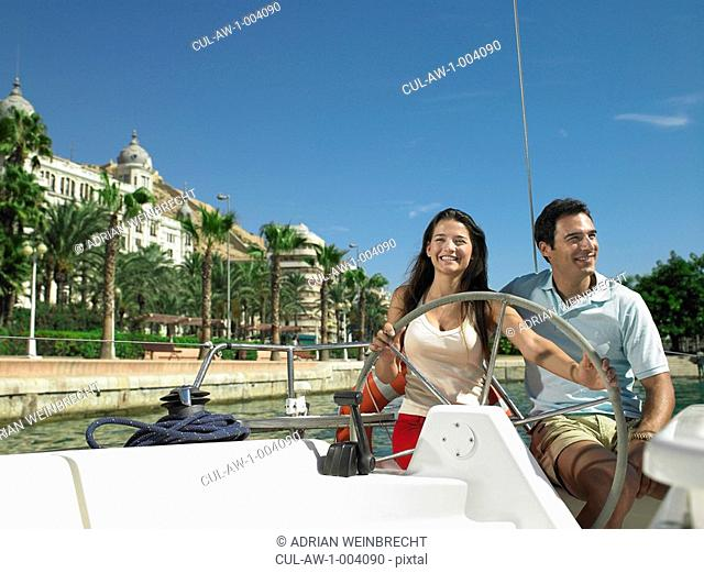 Young couple at wheel of yacht in marina, smiling