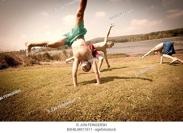 Caucasian boys doing cartwheels in grass
