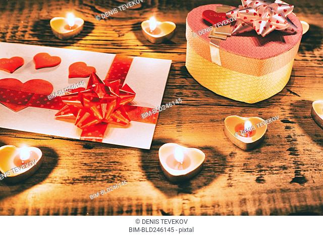 Valentine candles burning on table with gift box and card
