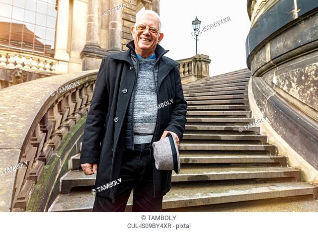 Senior man exploring city standing on stairway, Dresden, Sachsen, Germany