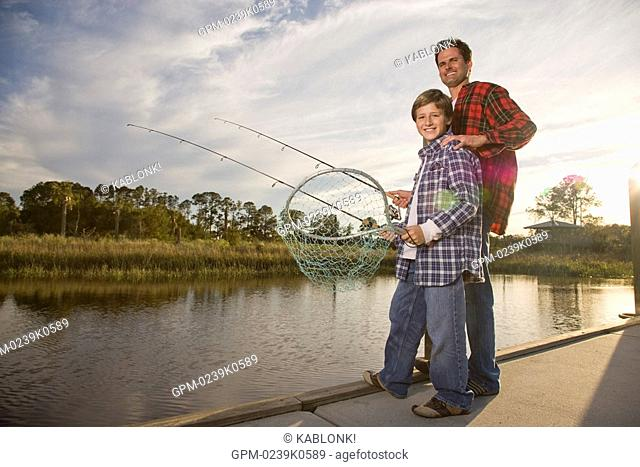 Portrait of happy son and father fishing by river