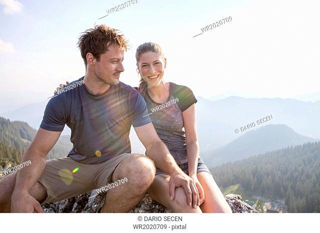 Young couple having fun on mountain peak