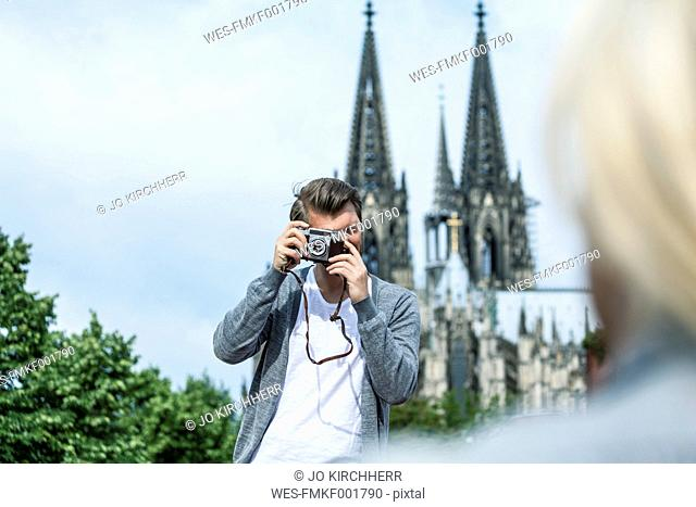 Germany, Cologne, man taking a picture of his girlfriend
