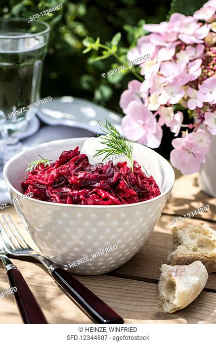 Red beet orzotto in a small bowl on a table outdoors