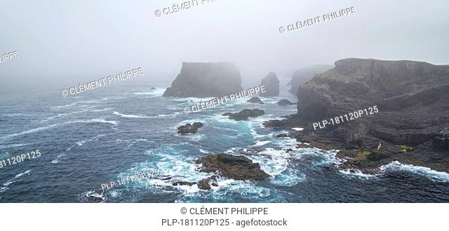 Sea stacks and sea cliffs in mist during stormy weather at Eshaness / Esha Ness, peninsula in Northmavine, Mainland, Shetland Islands, Scotland, UK