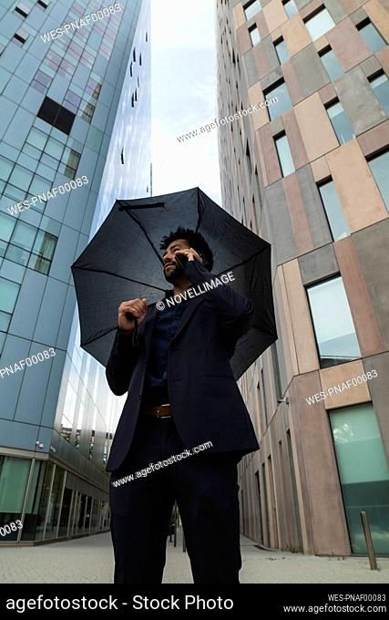 Entrepreneur with umbrella talking on smart phone against building in city